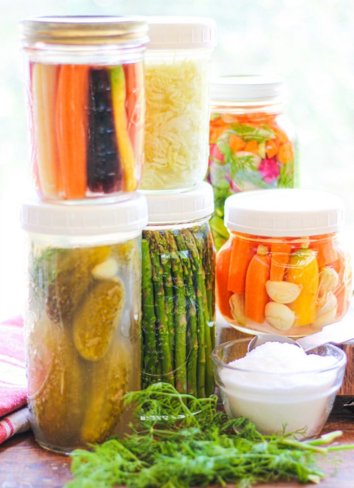 several jars of different kinds of fermented veggies stacked in a sunny window