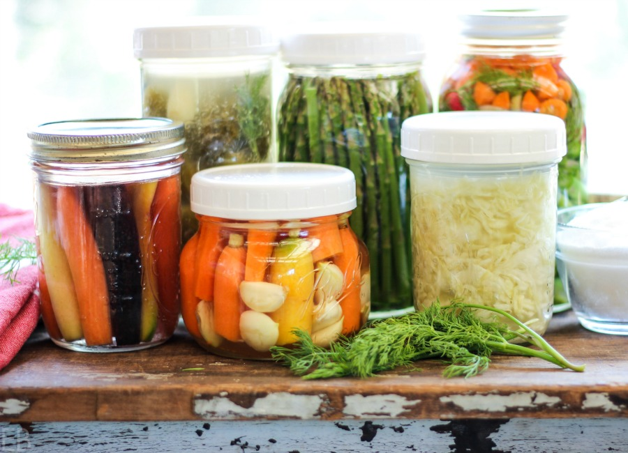 a row of jars lined up with different veggies inside