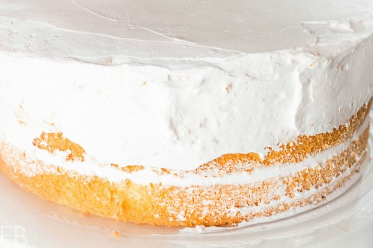 layers of yellow cake being frosting with stabilized whipped cream that's keto gaps diet low carb and paleo or primal