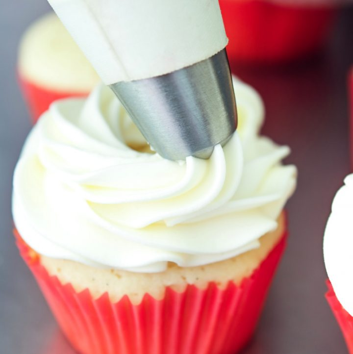 piping stabilized whipped cream onto a cupcake