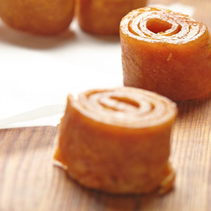 rolled up strips of winter squash fruit leather on a table