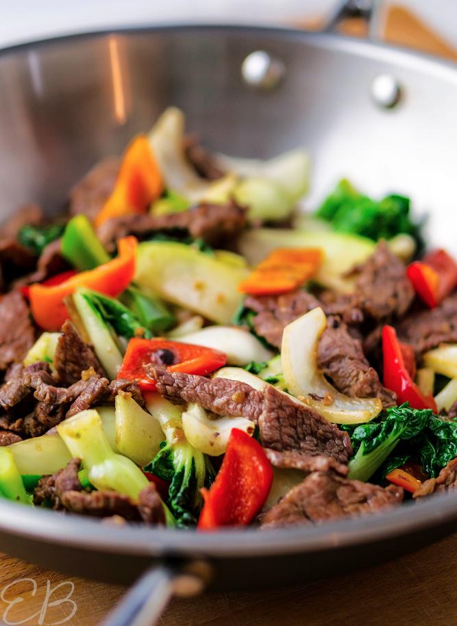steak stir fry in wok being cooked