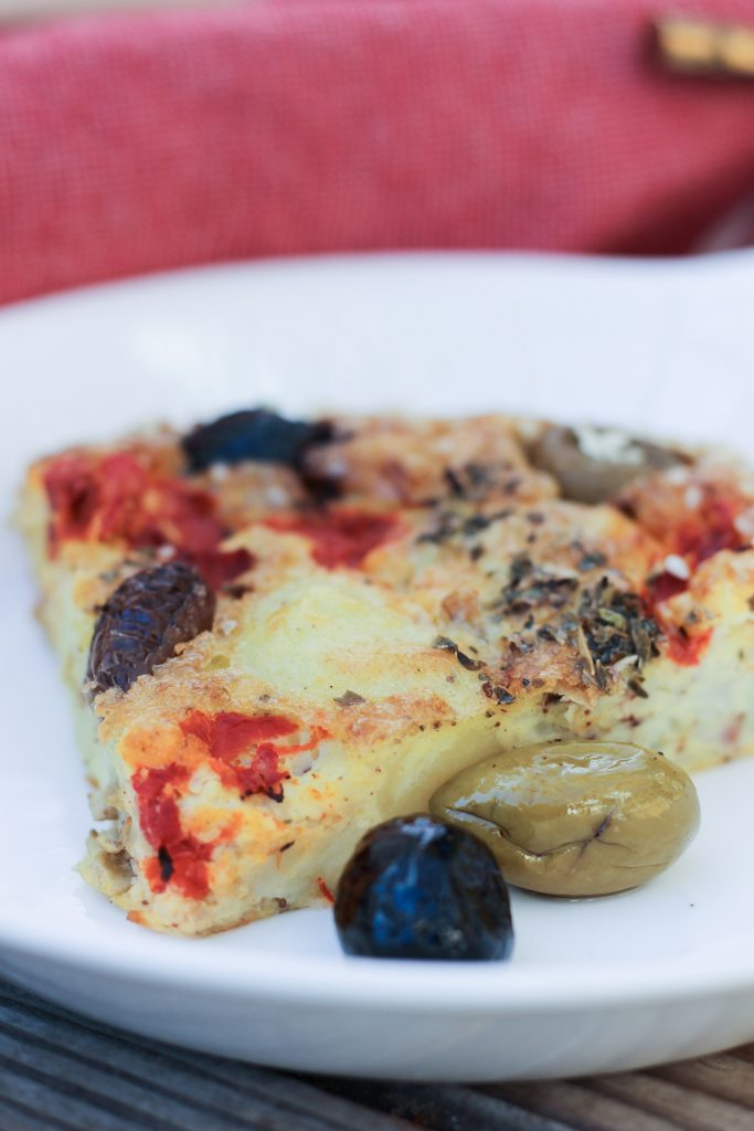 slice of whole30 quiche with olives on white plate