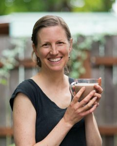 Photo of Megan Stevens holding bulletproof decaf coffee, from Eat Beautiful, at her Paleo, gut-healing cafe