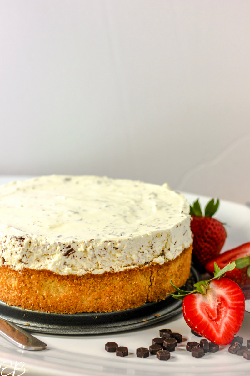whole chocolate chip cheesecake with white background and fresh strawberries