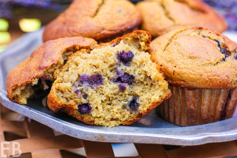 broken open paleo blueberry-banana high protein muffin on plate with other muffins