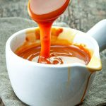 spoon pouring paleo aip caramel sauce into serving dish