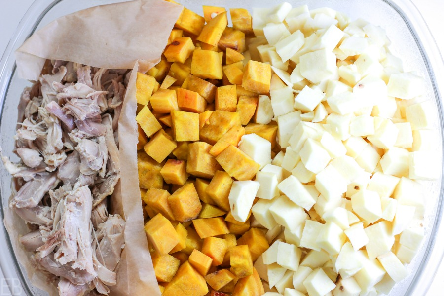 a glass storage container with cooked chicken and cubed root veggies; all this got prepped a day before the recipe was assembled to make it easier the night it was served.