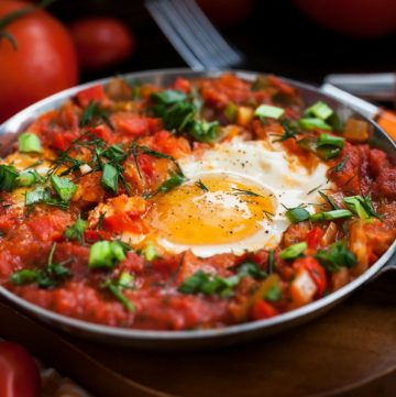 one pan of shakshuka and eggs surrounded by fresh tomatoes