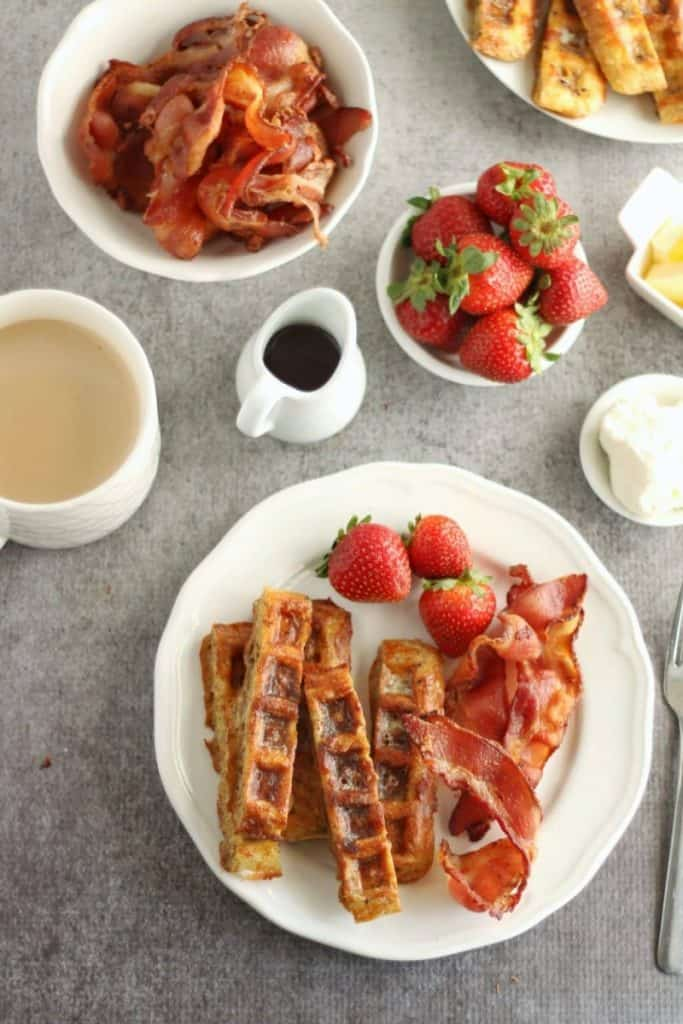 chaffle french toast sticks on white plates with fresh strawberries
