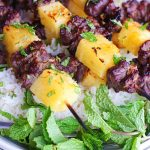 broiled thai beef kabobs on rice in white bowl with mint