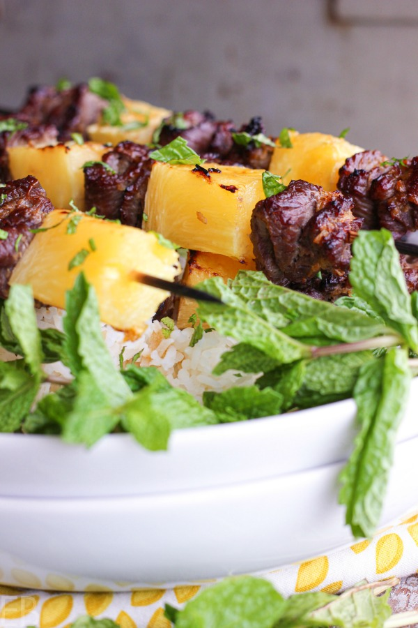 thai beef kabobs on white plates with fresh mint