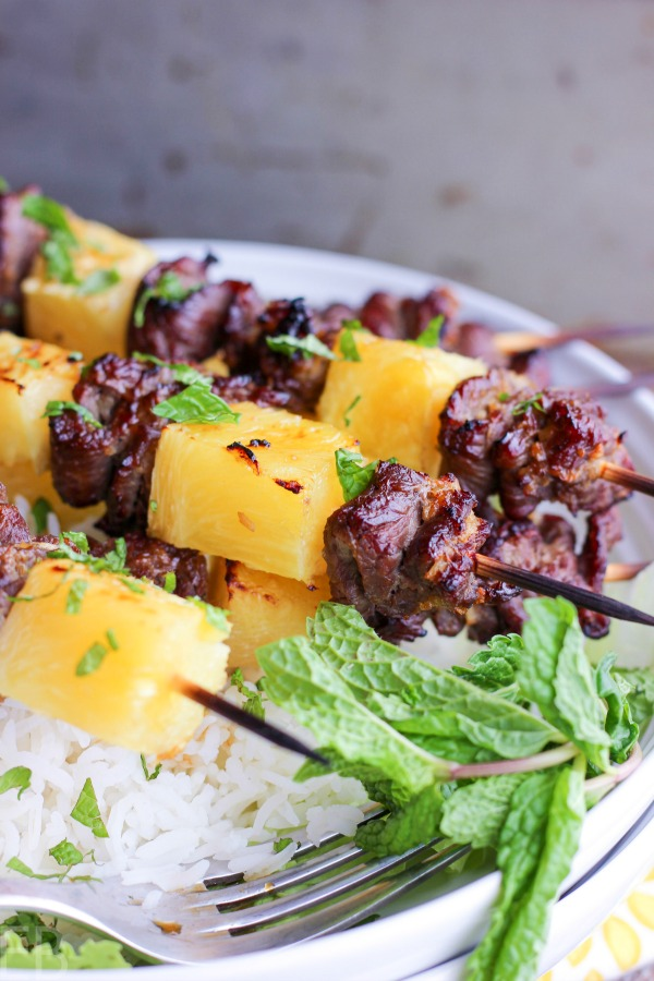 kabobs of beef sirloin and pineapple with fresh mint on white plate with rice
