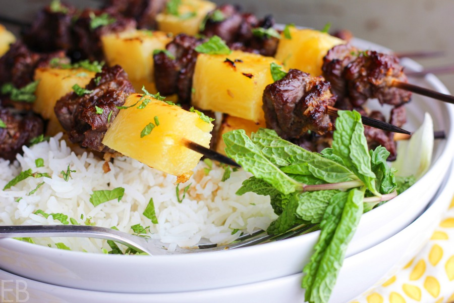 fresh pineapple and beef kabobs on white rice with fresh mint in white bowl