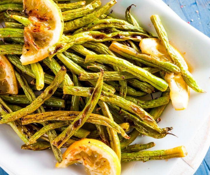 white dish of roasted green beans with lemon slices