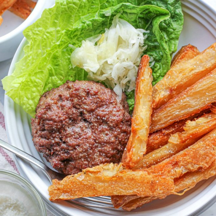 overhead view of aip burgers and fries in a white dish with lettuce and sauerkraut