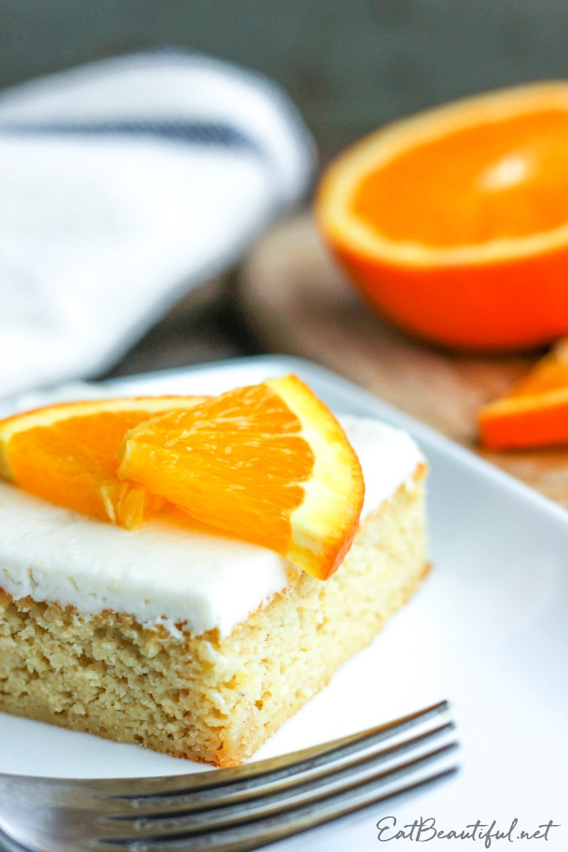 slice of keto orange creamsicle cake on white plate with fork