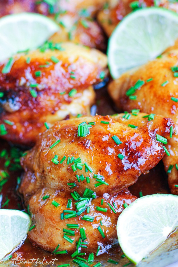 close up view of spicy honey lime chicken thighs with chives