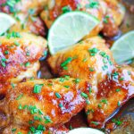 spicy honey lime chicken thighs with lime wedges in cooking pan