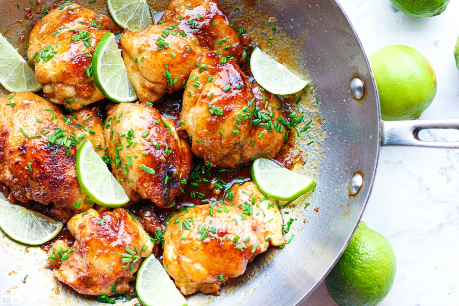 overhead view of pan with spicy honey lime chicken thighs and lime wedges
