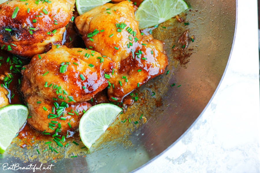 corner view of pan with spicy honey lime chicken thighs with chives and lime slices
