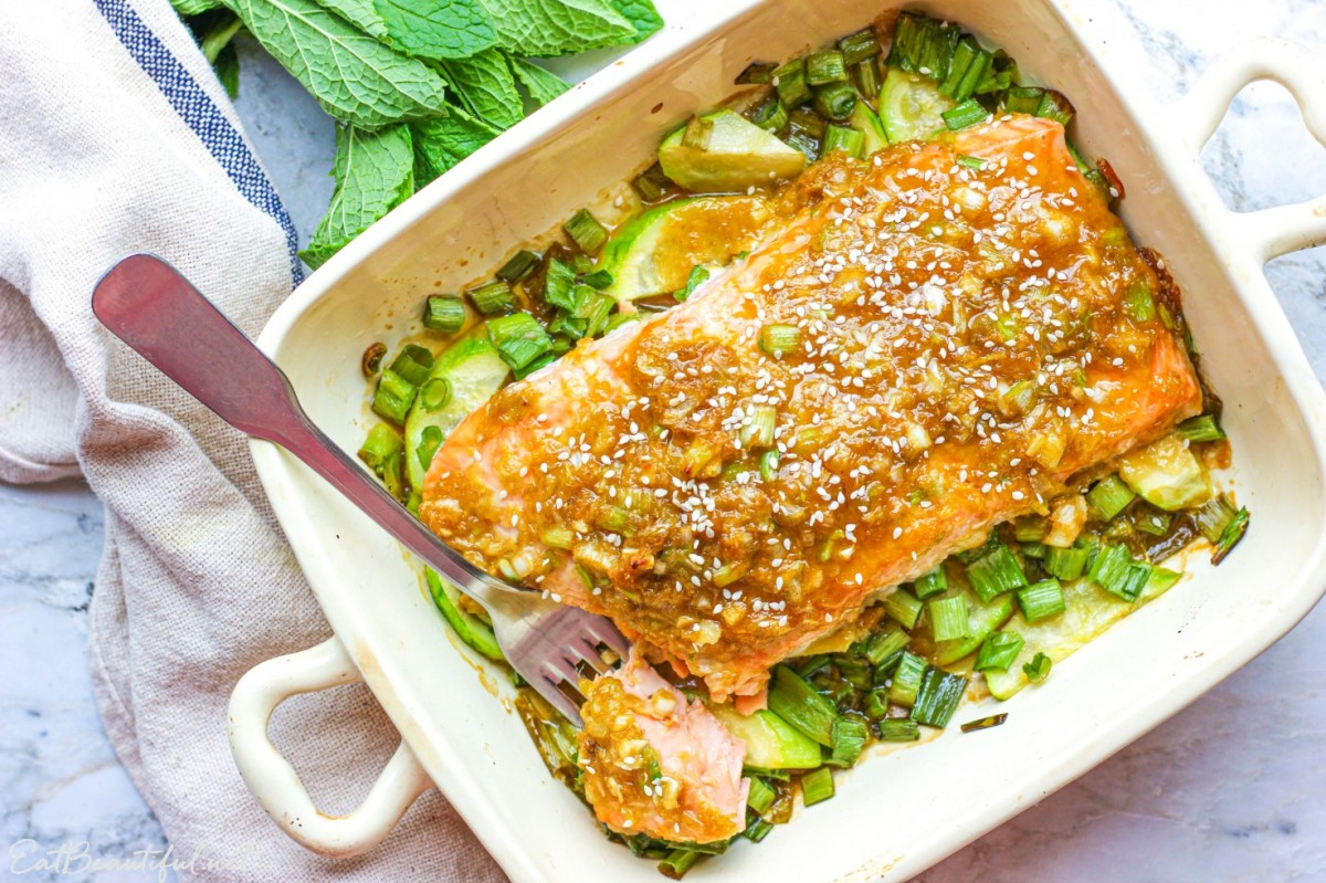 overhead view of ginger-lime salmon in baking dish with fork and one bite taken out