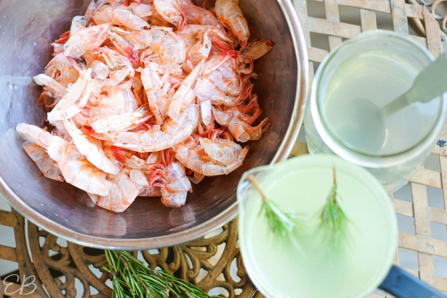 overhead view of cooked shrimp in bowl and shrimp stock with rosemary