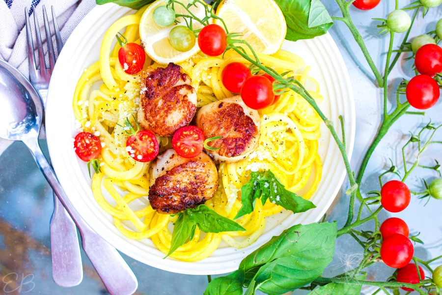 aerial view of scallop scampi with zucchini noodles and fresh basil leaves in white plate
