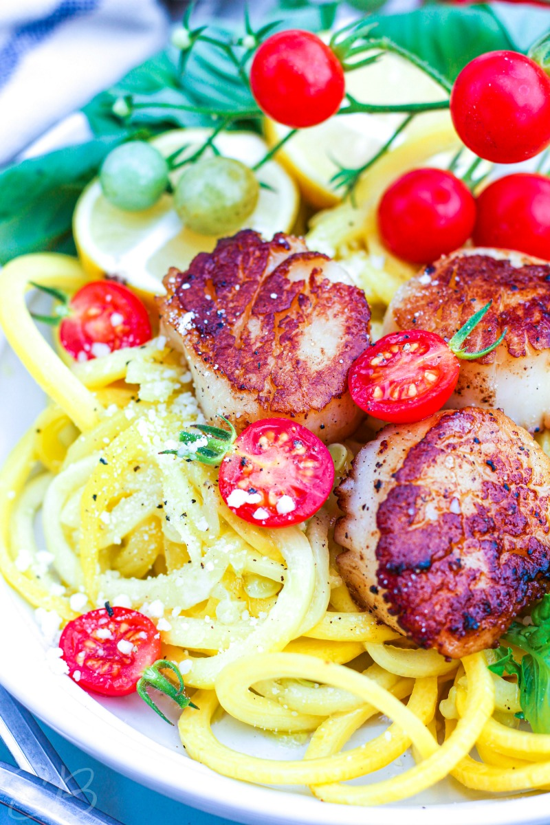 close up verticle image of scallop scampi with zoodles and tomatoes on the vine