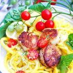 vertical image of scallop scampi with a branch of fresh tomatoes hanging over