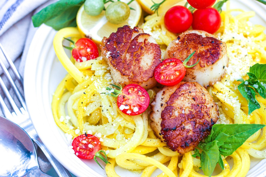 side image of scallop scampi with zucchini noodles, garnished with parmesan, tomatoes and basil