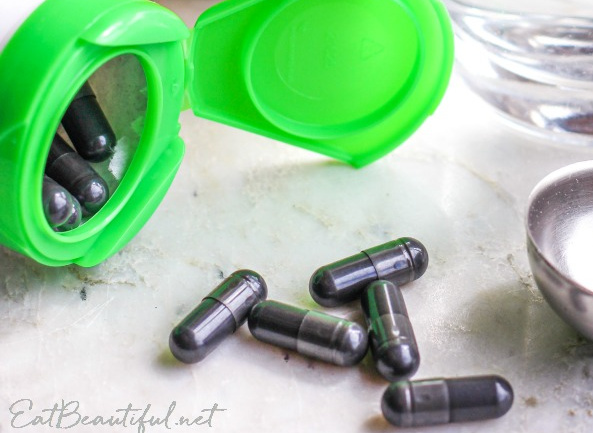 several activated charcoal pills and the container