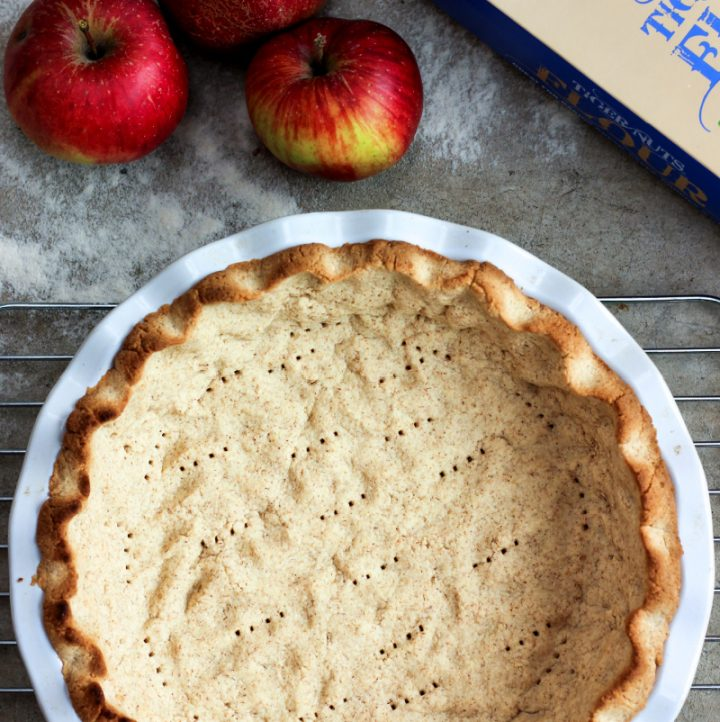 overhead view of tiger nut flour pie crust with apples and flour to one side