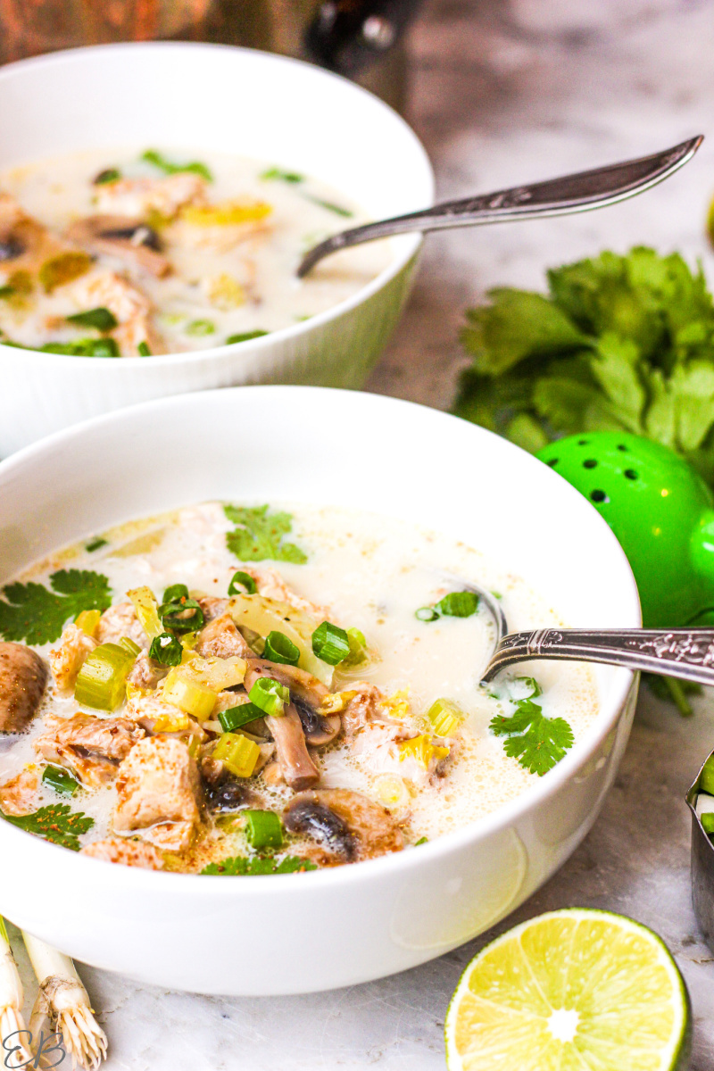 two bowls of aip tom kha gai, each with spoons