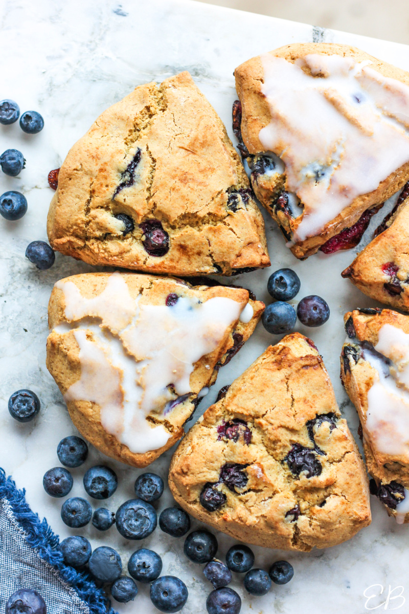 6 aip blueberry scones in a circle with fresh berries around