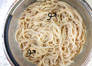spaghetti noodles in strainer sticking together in spots