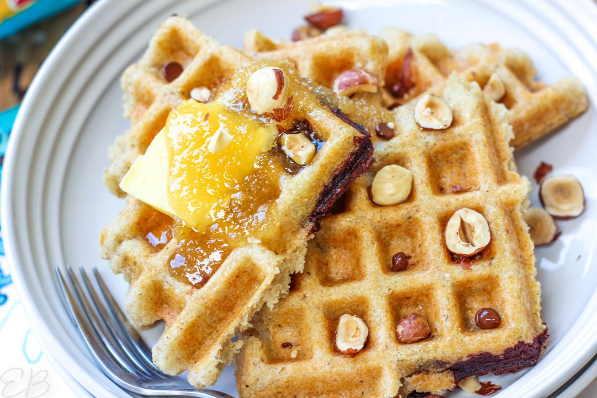 several bean and oat waffles piled on a plate with butter, honey, hazelnuts and chocolate chips on top