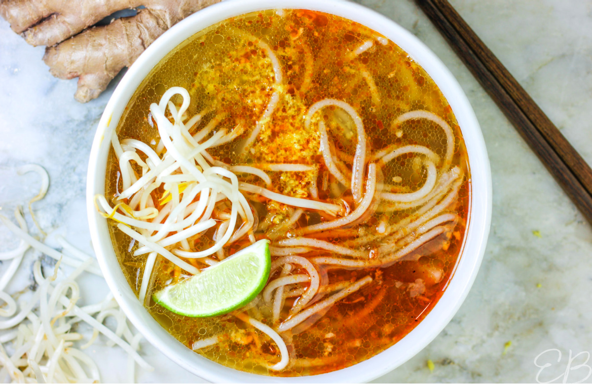 overhead view of bun bo hue with noodles, mung bean sprouts and lime