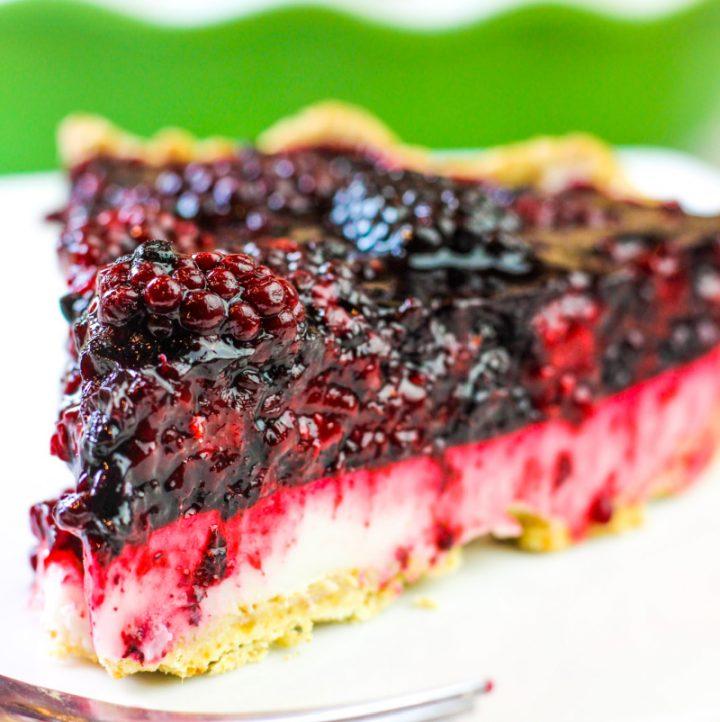 an up close photo of one slice served of blackberry lemon cream pie