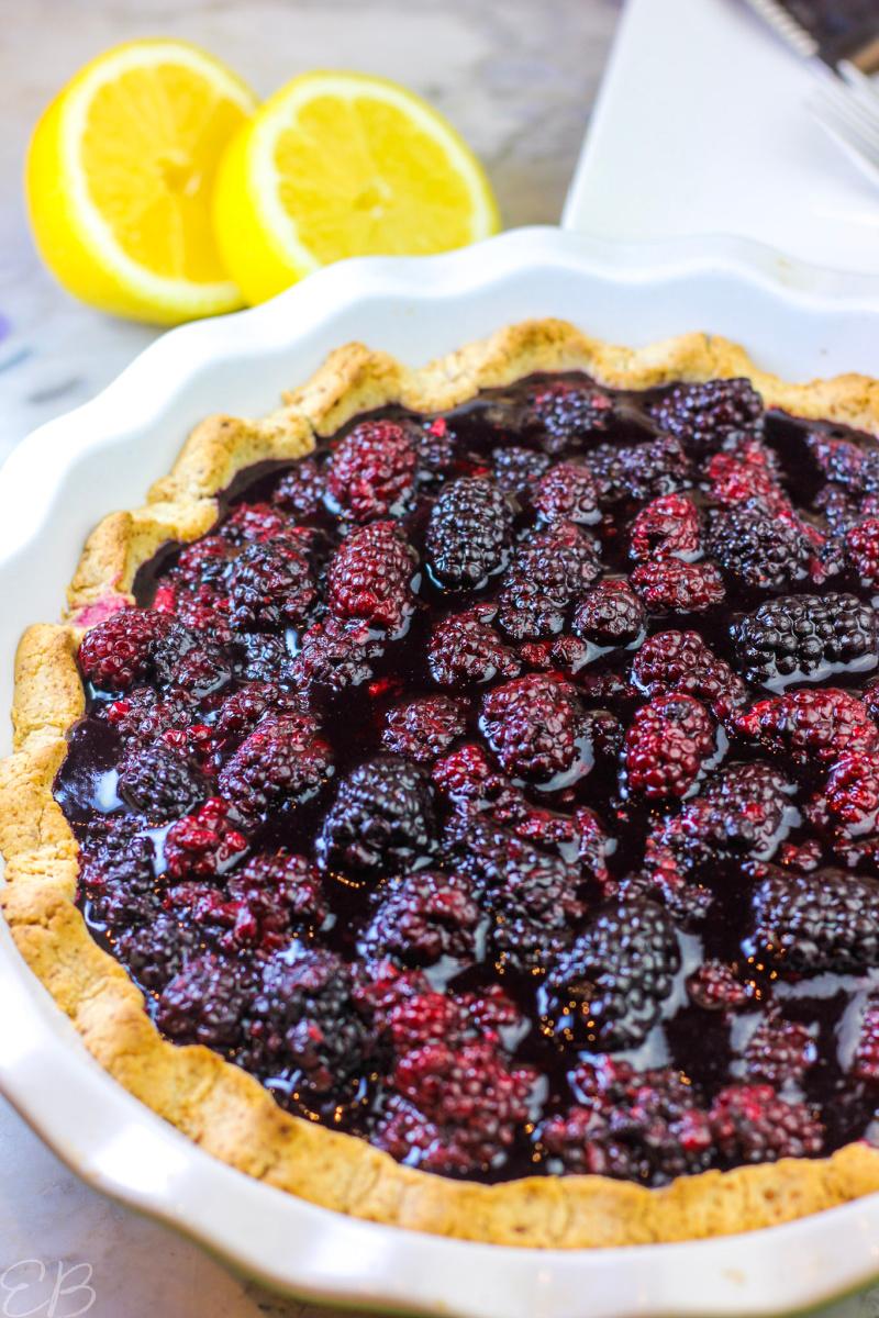 whole blackberry lemon cream pie with lemons in the background