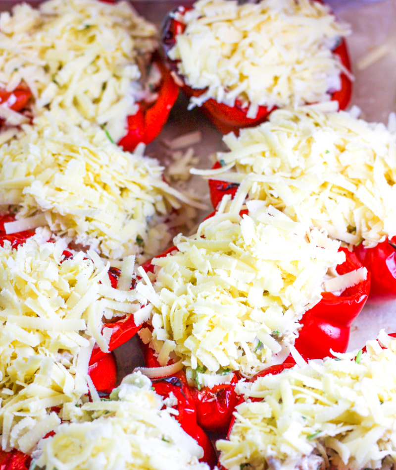 keto stuffed peppers topped with grated cheese before being baked