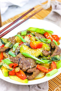 Paleo Beef Stir Fry served in a white dish with chop sticks.