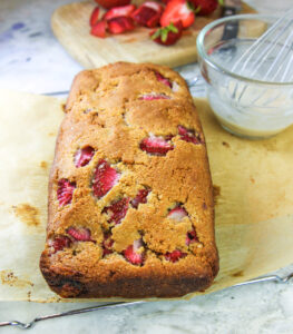 up close image of just baked keto vegan strawberry loaf with dish of optional glaze and whisk to one side