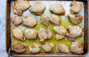 overhead view of baked chicken thighs on sheet pan