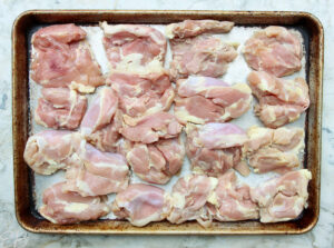 overhead view of raw chicken thighs spread out evenly on the sheet pan before being baked