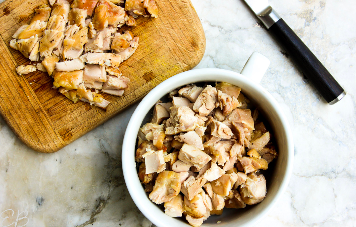 overhead view of chopping process of chicken thigh