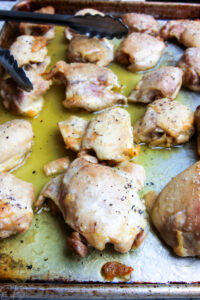 45 degree close up angle of fully baked meal prep sheet pan chicken thighs