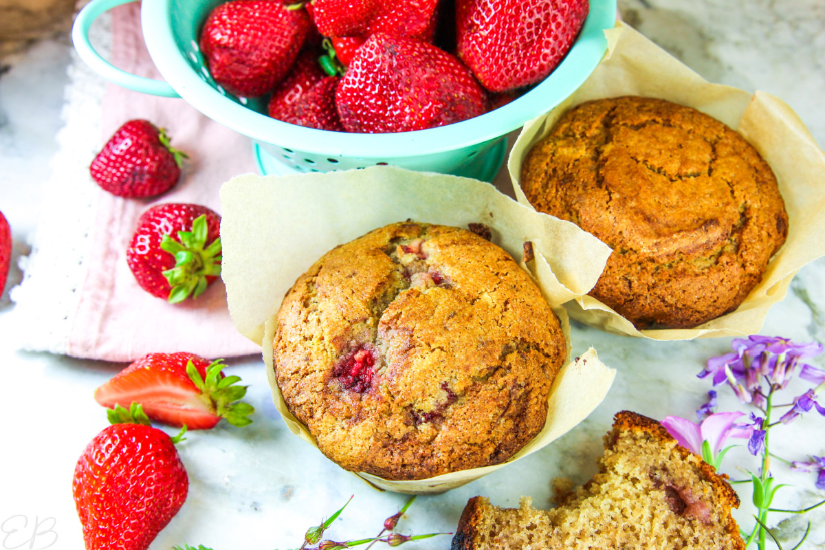 3 paleo strawberry muffins with fresh strawberries all around