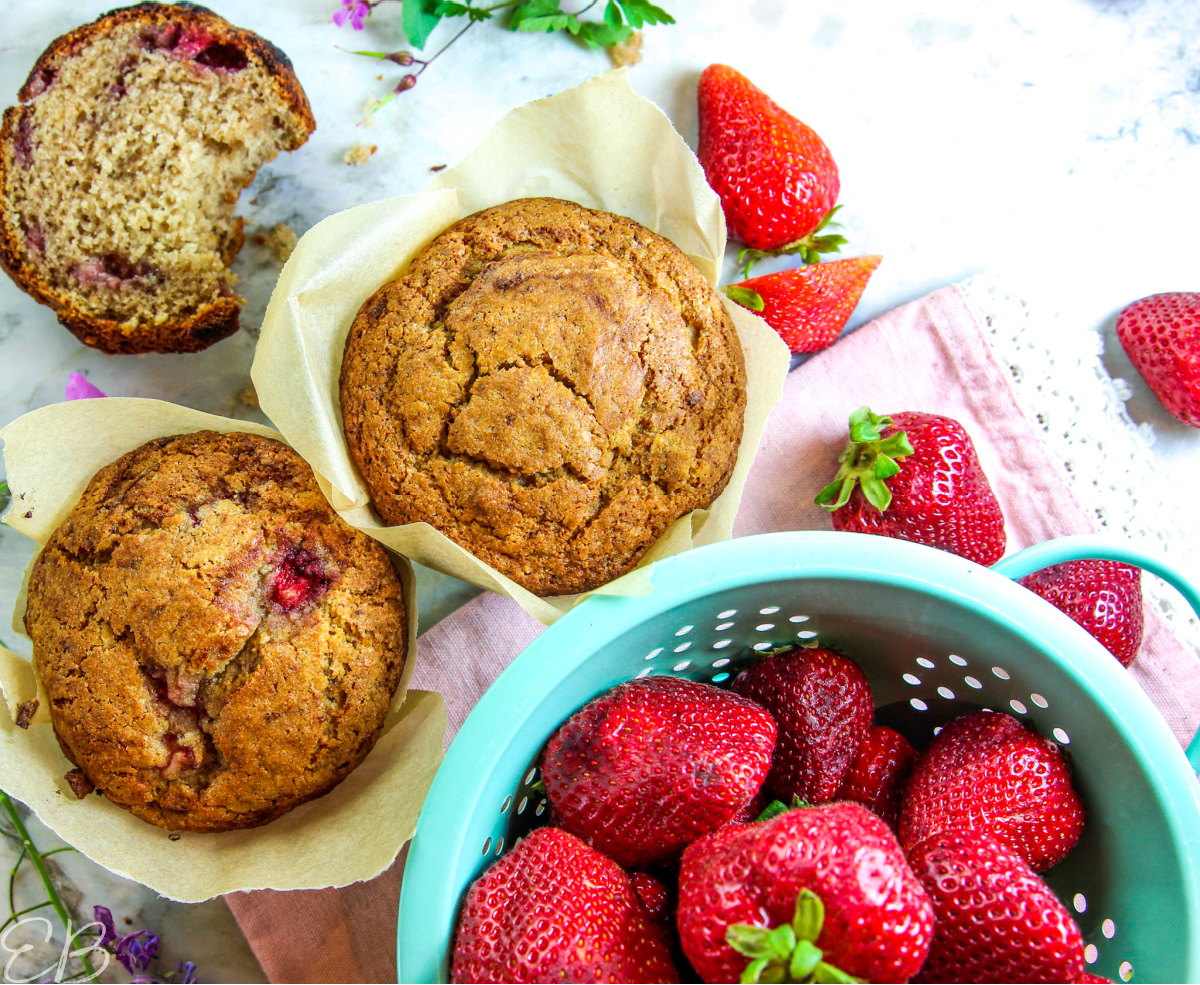 2 muffins and an overhead view of a colander of strawberries