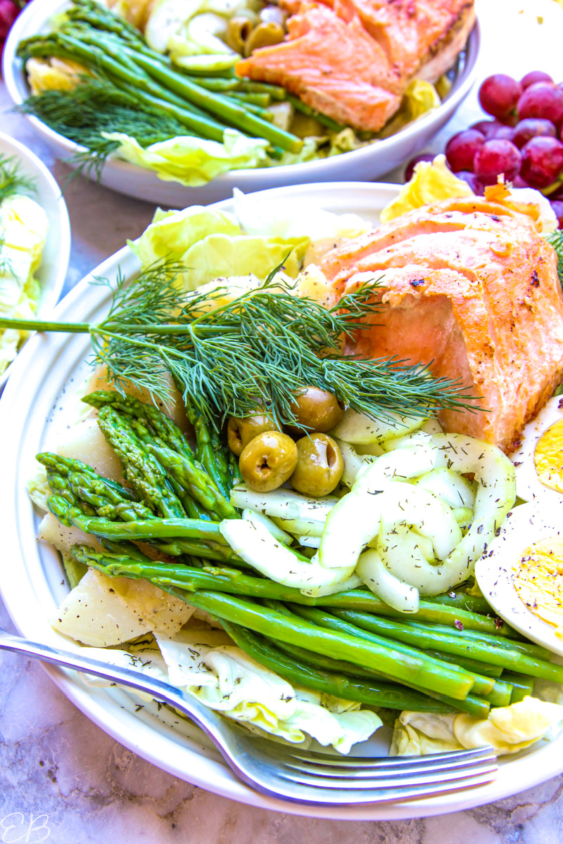 angled view of plated salad with asparagus, cucumbers, olives and salmon